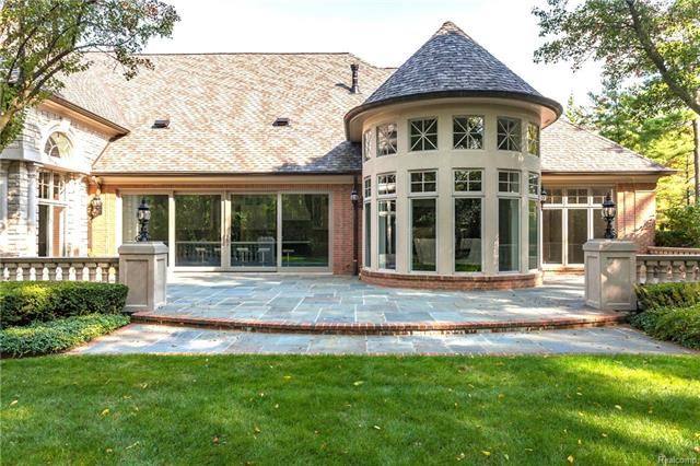 - Rear elevation showing brick trim on elevated bluestone patio and window detail in Florida Room